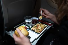 Close up of a plate of food served on the airplane. Woman eating rice salad, bread, fruits, tea, and water on an airplane stock photo