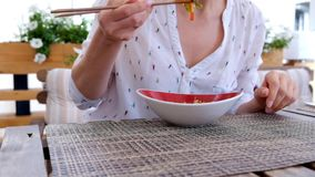 Woman eating rice with vegetables in an asian restaurant, close up stock video footage