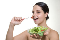 Woman eating salad. Young woman eating tomato in fork and showing salad plate on white background Royalty Free Stock Photography