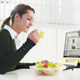 Woman eating salad. In office. Copy space Royalty Free Stock Photos