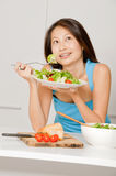 Woman Eating Salad. A good looking woman eating a healthy meal of bread and salad in her kitchen royalty free stock image
