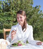 Woman eating salad. Young woman eating a healthy salad outdoors on restaurant patio Stock Photography
