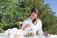Woman eating salad. Young woman eating a healthy salad outdoors on restaurant patio Royalty Free Stock Photos