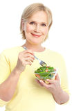 Woman eating salad. Mature smiling woman  eating salad,  fruits and vegetables Royalty Free Stock Photography