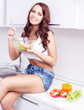 Woman eating salad Stock Photos