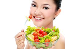 Woman eating salad. Closeup portrait of an attractive young woman eating vegetable salad Royalty Free Stock Images