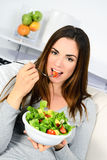 Woman eating salad. Beautiful healthy smiling Caucasian woman enjoying a fresh healthy salad sitting in sofa looking up. High angle view with copy space on Stock Image