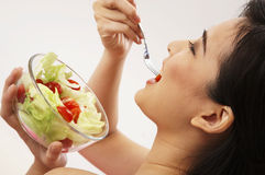 Woman eating salad Stock Images