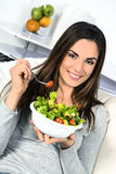 Woman eating salad. Beautiful healthy smiling Caucasian woman enjoying a fresh healthy salad sitting in sofa looking up. High angle view with copy space on Royalty Free Stock Image