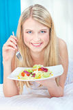 Woman eating salad in bed. Pretty smiled woman eating salad in bed royalty free stock image