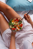 Woman eating salad in the bed Royalty Free Stock Photography