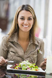Woman eating salad at cafe. Woman eating plate of salad at cafe Stock Photos