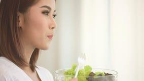 Woman eating salad stock video