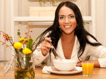 Woman eating salad at home Stock Images