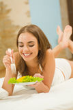 Woman eating salad at home Stock Image