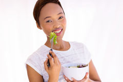 Woman eating salad home. Close up portrait of healthy young african woman eating green salad at home Royalty Free Stock Photos
