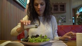 Woman eating salad in an indoor cafe, close up on a plate. Woman eating salad in an indoor cafe, close up on the plate stock video