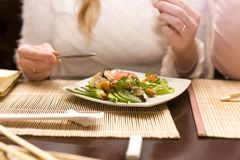 Woman eating salad in japanese restaurant. Focus on dish Royalty Free Stock Photography