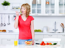 Woman  eating salad in the kitchen Stock Image