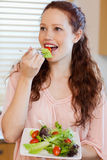 Woman eating salad in the kitchen Stock Photography