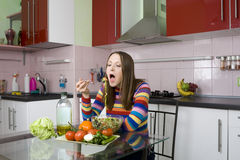 Woman eating salad in the kitchen Stock Photo