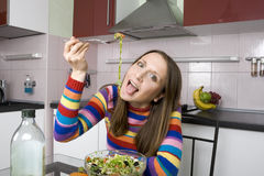 Woman eating salad on the kitchen Stock Photos