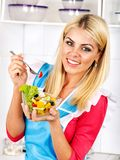 Woman eating salad at kitchen. Stock Images