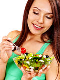 Woman eating salad at kitchen. Stock Photography