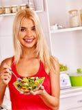Woman eating salad at kitchen Royalty Free Stock Image