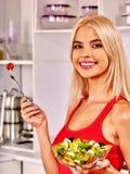 Woman eating salad at kitchen Royalty Free Stock Images