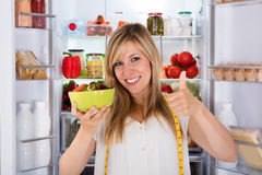 Woman Eating Salad Near Refrigerator Royalty Free Stock Images