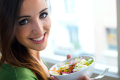 Woman eating salad. Portrait of beautiful smiling and happy Cauc Royalty Free Stock Photos