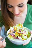 Woman eating salad. Portrait of beautiful smiling and happy Cauc Stock Photos