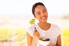 Woman eating salad. Pretty young black woman eating salad outdoors Royalty Free Stock Photography