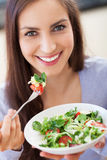 Woman eating salad. And smiling Stock Images