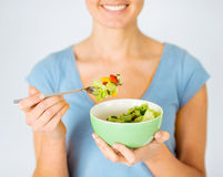 Woman eating salad with vegetables Royalty Free Stock Image