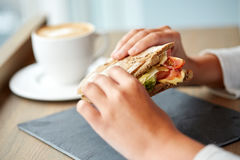 Woman eating salmon panini sandwich at restaurant royalty free stock photography