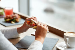 Woman eating salmon panini sandwich at restaurant Royalty Free Stock Photos