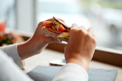 Woman eating salmon panini sandwich at restaurant Stock Photography