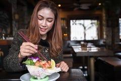 Woman eating salmon sashimi spicy salad in restaurant stock photos