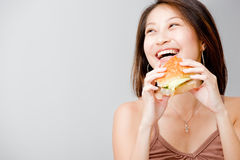 Woman Eating Sandwich. A good looking woman having a sandwich against white background royalty free stock image