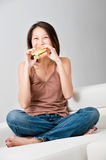 Woman Eating Sandwich. A good looking woman having a sandwich on her couch at home royalty free stock photos