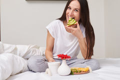 Woman eating sandwich in bed stock photo