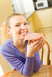 Woman eating sandwich at home Royalty Free Stock Images