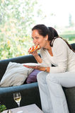 Woman eating sandwich lunch breakfast home sofa royalty free stock photos