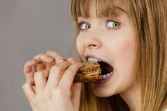 Woman eating sandwich, taking bite. Young woman eating sandwich, taking bite with wide open mouth. Food, calories, dieting concept. Studio shot on grey Royalty Free Stock Photos