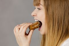 Woman eating sandwich, taking bite. Young woman eating sandwich, taking bite with wide open mouth. Food, calories, dieting concept. Studio shot on grey Royalty Free Stock Images