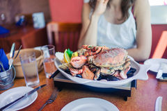 Woman eating seafood platter. A young woman is having a large seafood platter for lunch Stock Photography