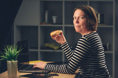 Woman eating sesame bagel in office. While working overtime on laptop computer stock photo