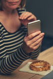 Woman eating sesame bagel and using mobile phone Stock Image
